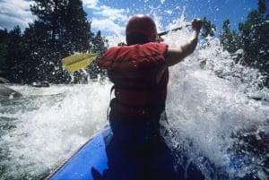 View of kayaker from behind on whitewater rapids