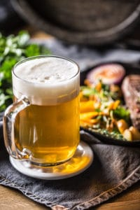 Pub glass of beer with plate of food in background at Duluth Restaurants